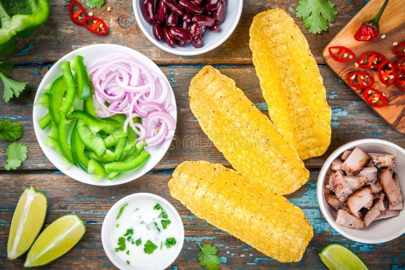 Tacoingredienser: grönsaker, griskött med sås och limefrukt arkivfoto