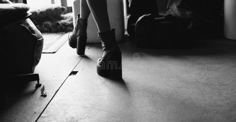 Tacones altos americanos del eje de balancín de la muchacha y chaquetas de cuero negras Textura de la película y unfocused fotos de archivo