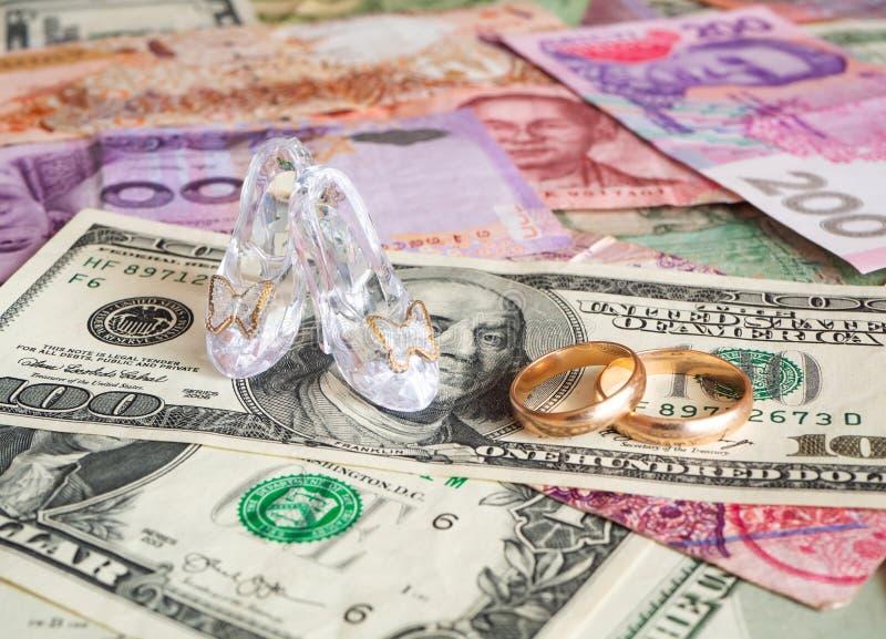 Tacones altos y anillos de bodas en diversas monedas Boda de la conveniencia foto de archivo