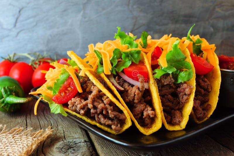 Tacos écossé dur avec le boeuf haché, les légumes et le fromage, fin vers le haut de scène photographie stock libre de droits