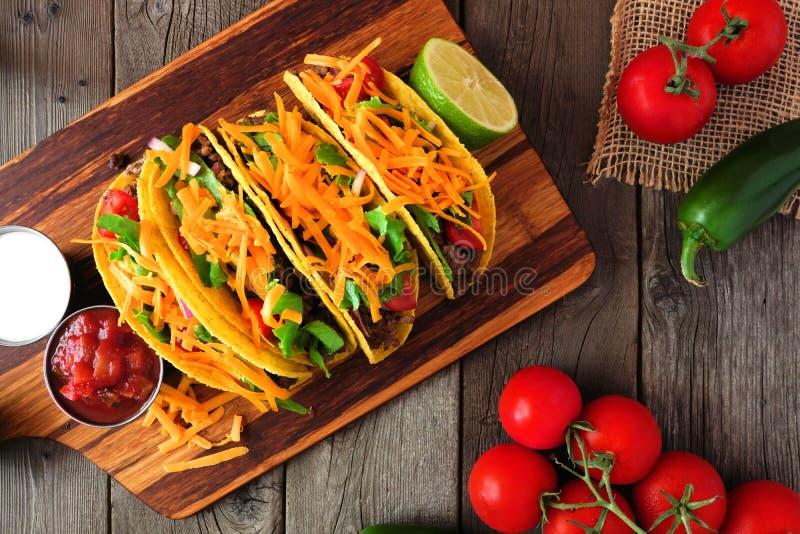 Tacos écossé dur avec le boeuf haché, les légumes et le fromage, scène aérienne dessus au-dessus de bois image stock
