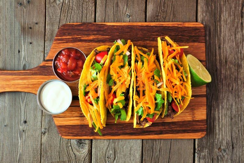 Tacos écossé dur avec le boeuf haché, les légumes et le fromage, vue supérieure sur un fond en bois image libre de droits