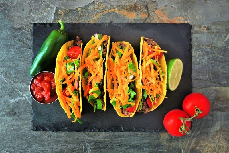 Tacos écossé dur avec le boeuf haché, les légumes et le fromage, vue supérieure sur un fond foncé images stock