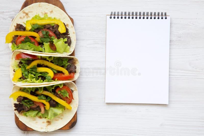 Tacos avec du porc et des légumes avec le carnet Cuisine mexicaine Fond en bois blanc vue supérieure, image libre de droits