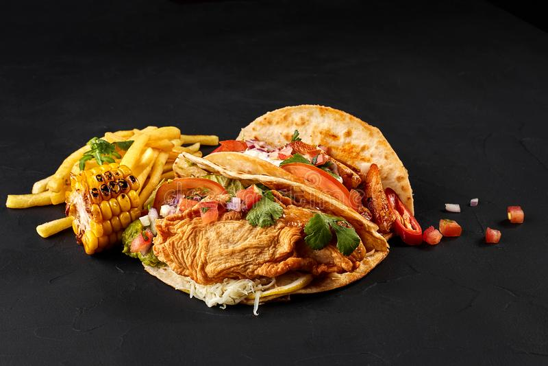 Tacos avec le poulet, la tomate et les légumes frais et la sauce à tartre sur le fond noir photos stock