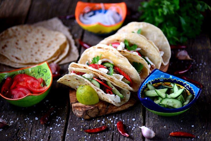Tacos caseiros com carne triturada no molho de tomate com tomates frescos, pepinos, pimentão e queijo macio Alimento mexicano foto de stock