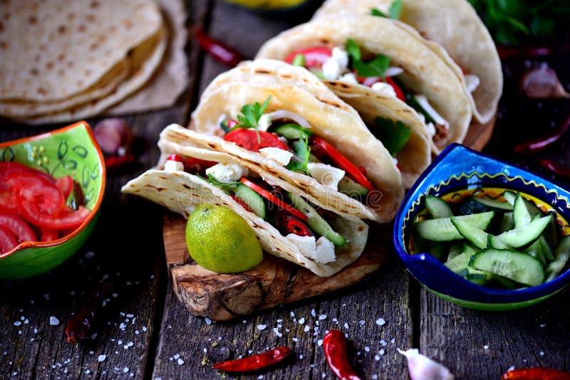 Tacos caseiros com carne triturada no molho de tomate com tomates frescos, pepinos, pimentão e queijo macio Alimento mexicano imagem de stock royalty free