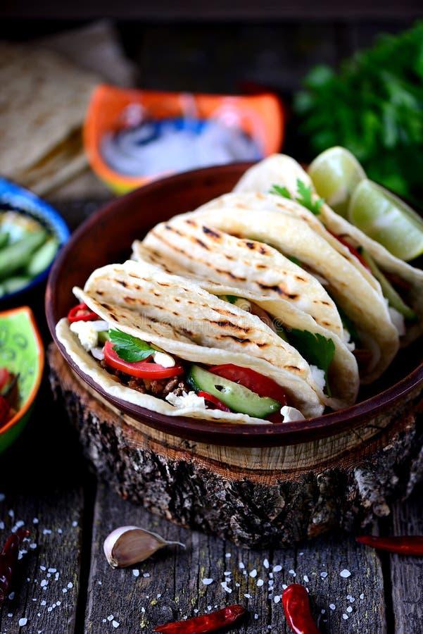 Tacos caseiros com carne triturada no molho de tomate com tomates frescos, pepinos, pimentão e queijo macio Alimento mexicano imagem de stock