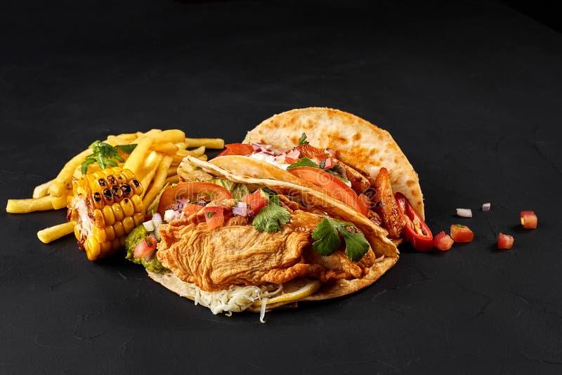 Tacos com galinha, tomate e legumes frescos e molho de tártaro no fundo preto fotos de stock