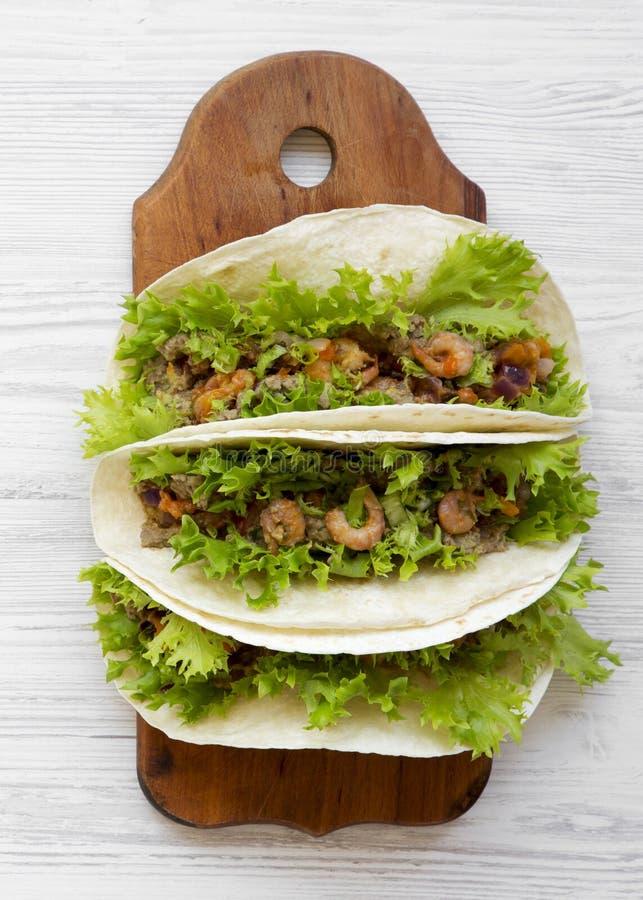 Tacos de crevette sur le conseil en bois au-dessus du fond en bois blanc, vue aérienne Nourriture mexicaine Configuration plate,  photo libre de droits
