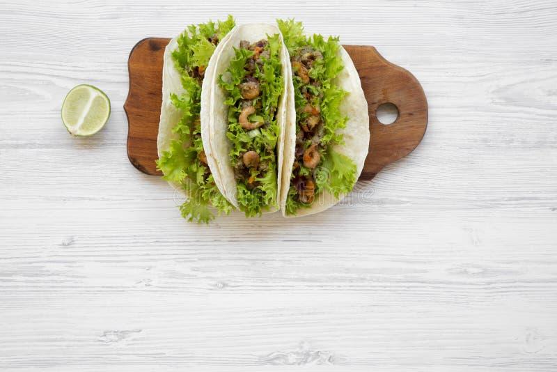 Tacos de crevette sur le conseil en bois sur la surface en bois blanche, vue supérieure Cuisine mexicaine Configuration plate, aé photographie stock