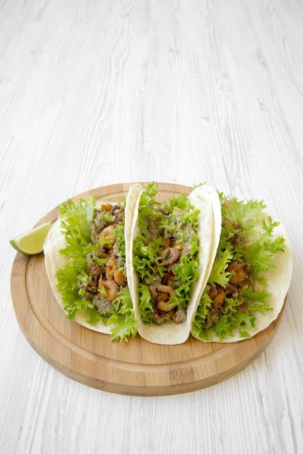 Tacos de crevette sur le panneau en bambou rond sur la table en bois blanche, vue de côté Cuisine mexicaine photo stock