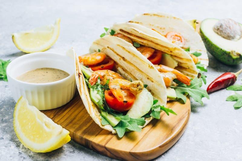 Tacos de tortilla avec l'arugula, le citron, l'avocat et les gages grill?s de crevette image libre de droits