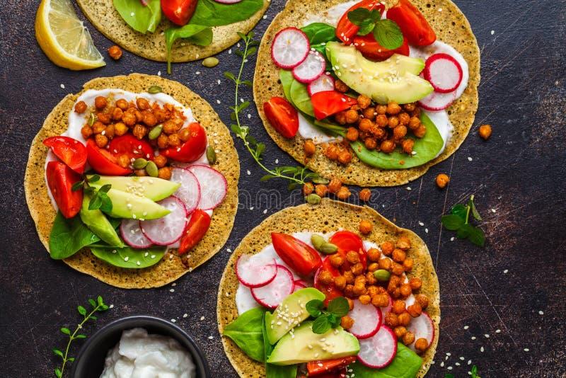 Tacos de Vegan avec les pois chiches, l'avocat, la sauce et les légumes cuits au four sur le fond foncé, vue supérieure images libres de droits