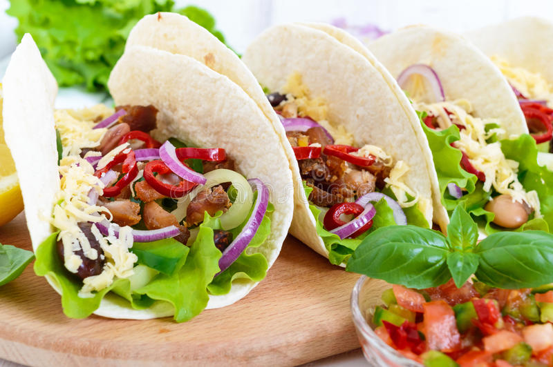 Tacos jest tradycyjnym Meksykańskim naczyniem Tortilla faszerował z kurczaka, dzwonkowych i gorących pieprzami, fasole, sałata, s obrazy stock