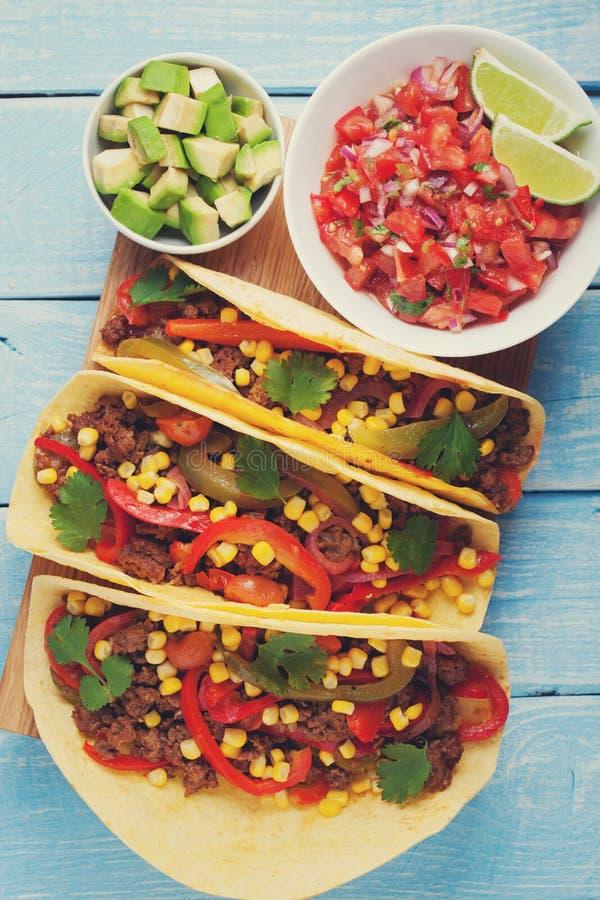Tacos mexicain avec du boeuf, les légumes et le Salsa hachés Pasteur d'Al de Tacos sur le fond rustique bleu en bois Vue supérieu images libres de droits