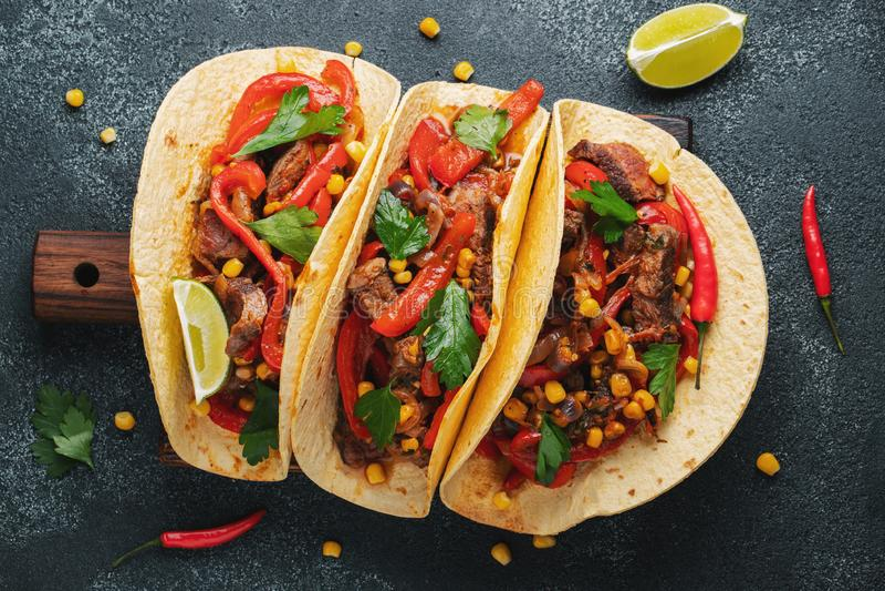 Tacos mexicain avec du boeuf, les légumes et le Salsa Pasteur d'Al de Tacos sur le conseil en bois sur le fond noir Vue supérieur image libre de droits