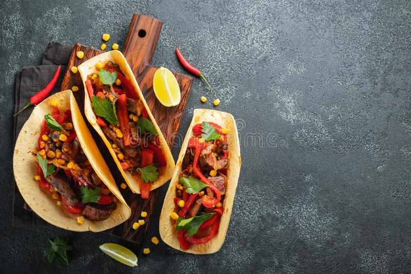 Tacos mexicain avec du boeuf, les légumes et le Salsa Pasteur d'Al de Tacos sur le conseil en bois sur le fond noir Vue supérieur images stock