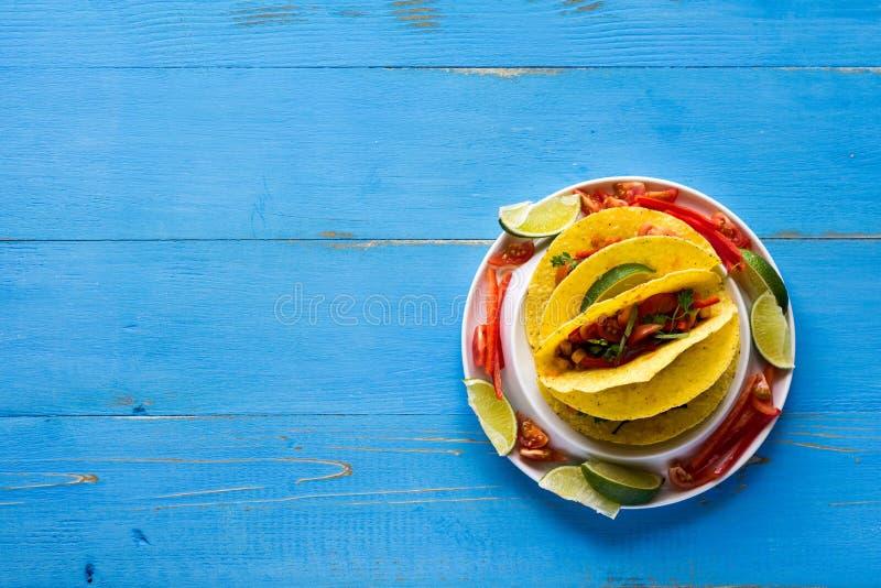 Tacos mexicain avec le boeuf haché et les légumes sur le fond bleu rustique photographie stock libre de droits