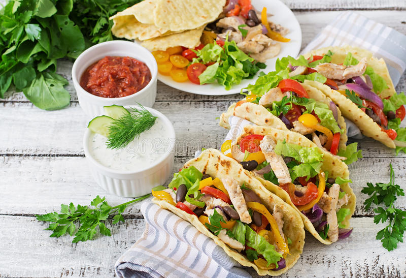 Tacos mexicain avec le poulet, les paprikas, les haricots noirs et les légumes frais photos libres de droits