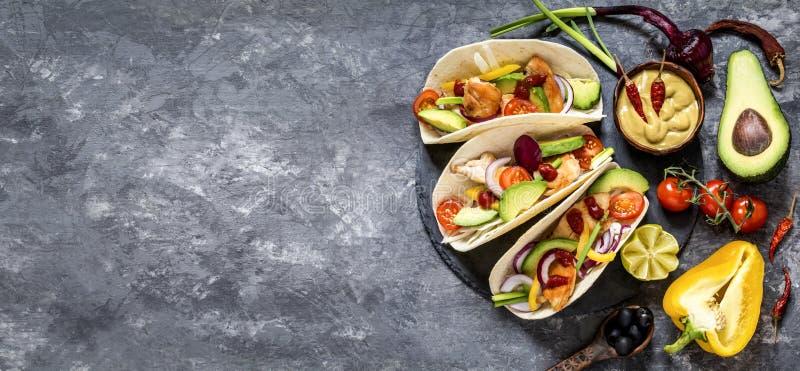 Tacos mexicain de nourriture, poulet frit, verts, avocat, poivre, chou rouge et avocat en tortillas photo libre de droits
