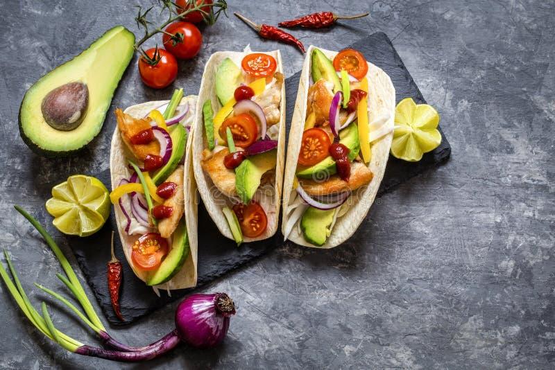 Tacos mexicain de nourriture, poulet frit, verts, avocat, poivre, chou rouge et avocat en tortillas images libres de droits