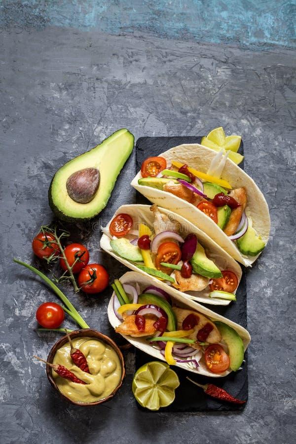 Tacos mexicain de nourriture, poulet frit, verts, avocat, poivre, chou rouge et avocat en tortillas photos stock