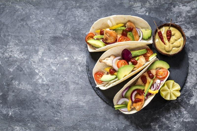 Tacos mexicain de nourriture, poulet frit, verts, avocat, poivre, chou rouge et avocat en tortillas images stock