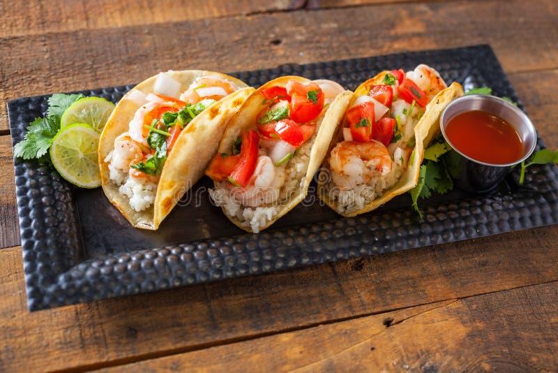 Tacos mexicain de rue avec la crevette, le riz et le Salsa dans le maïs jaune photographie stock