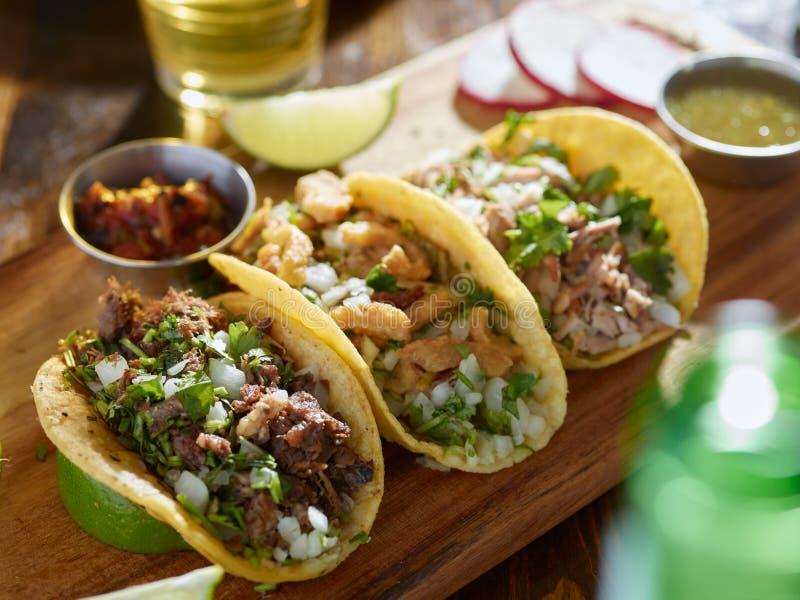 Tacos mexicain de rue avec le barbacoa, les carnitas et le ³ n de Chicharrà images libres de droits