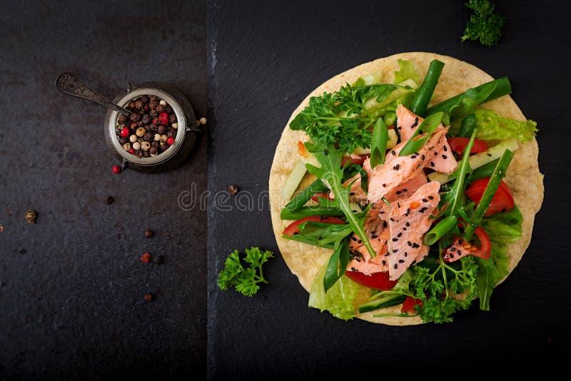 Tacos mexicain sain de maïs avec les saumons, la laitue, la tomate, le concombre et l'arugula cuits au four photographie stock libre de droits