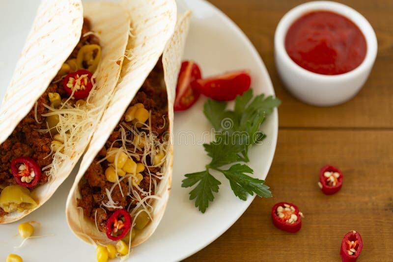 Tacos mexicain traditionnel avec de la viande et légumes, sauce tomate épicée et fromage d'un plat images libres de droits