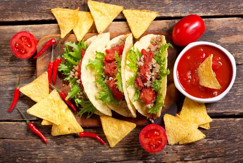 Tacos mexicanos con la carne y los nachos en una tabla de madera fotos de archivo