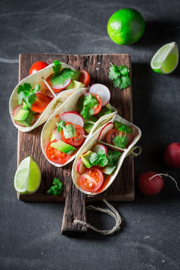 Tacos savoureux avec l'avocat et la coriandre fraîche sur la table concrète photo libre de droits