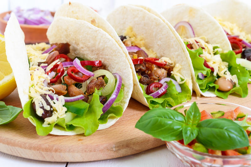 Tacos is a traditional Mexican dish. Tortilla stuffed with chicken, bell and hot peppers, beans, lettuce, cheese. Blue onion with salsa sauce on white wooden stock photos