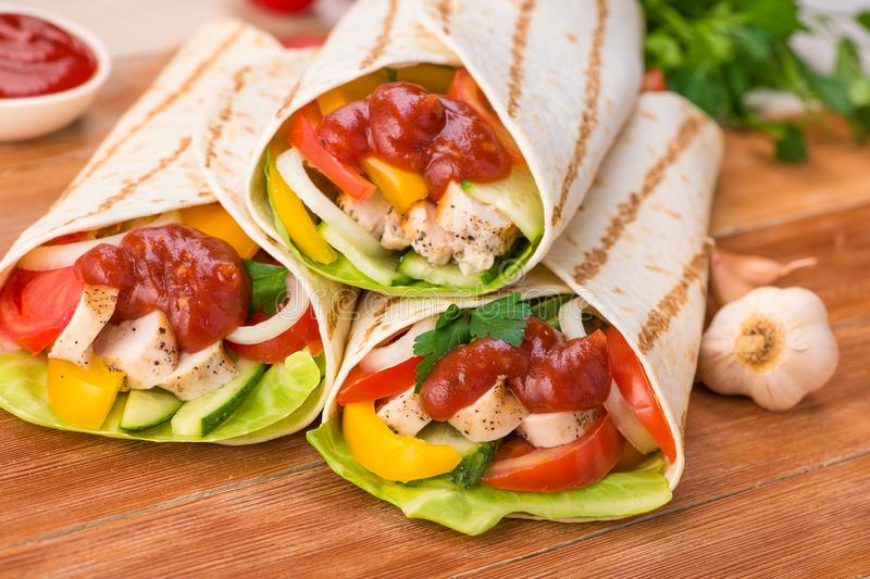 Tacos wraps with grilled chicken and fresh vegetables. On a wooden table. Mexican fast food background stock image