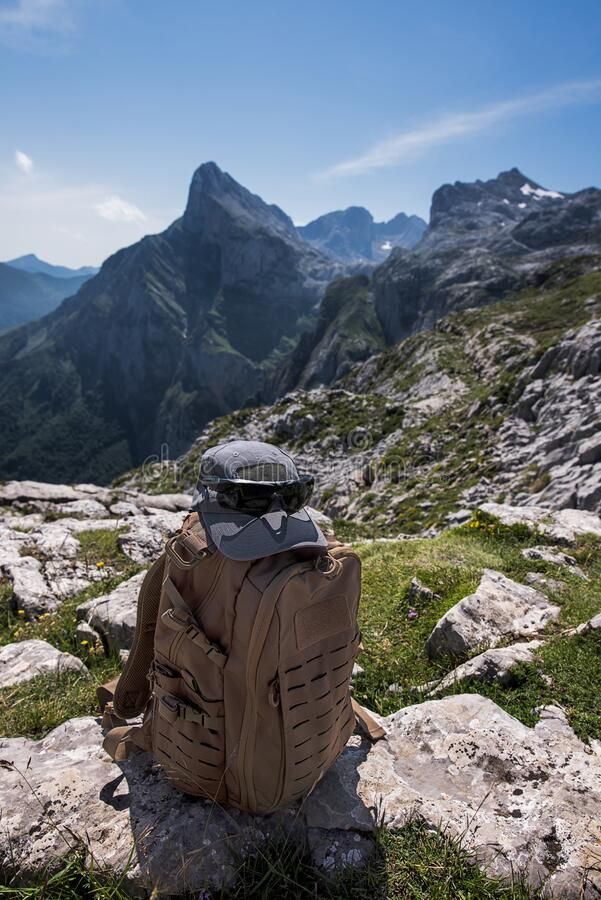 Tactical backpack, ballistic glasses and cap on mountains background. During a hiking march royalty free stock photo