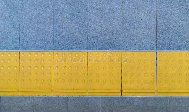 Tactile paving for blind handicap on tiles footpath. royalty free stock image