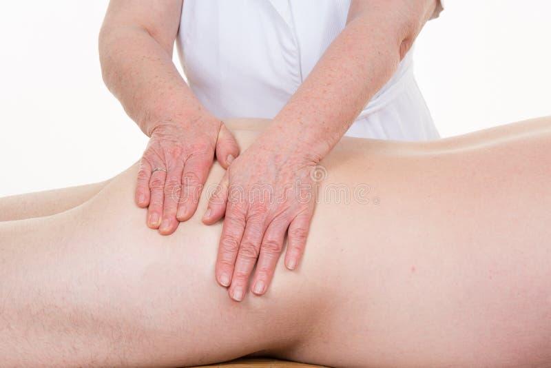 Tacto curativo de las manos de un ostheopath en el cuerpo del hombre imagenes de archivo
