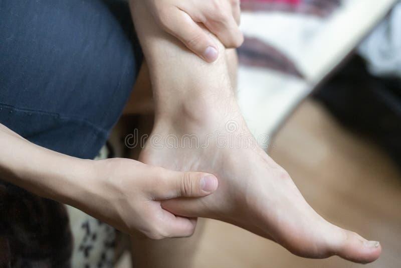 Tacto de la mano de la persona el tobillo, sintiendo un dolor óseo f fotos de archivo