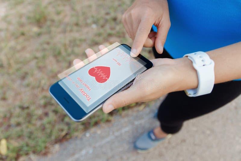 Tacto de la mujer del deporte en tecnología transparente del futuro de la exhibición del teléfono elegante imagen de archivo libre de regalías