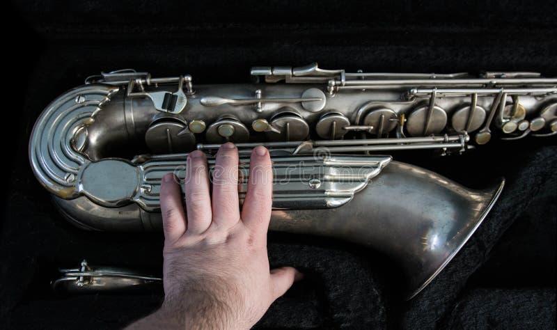Tacto de un saxofón de plata en su caso fotografía de archivo