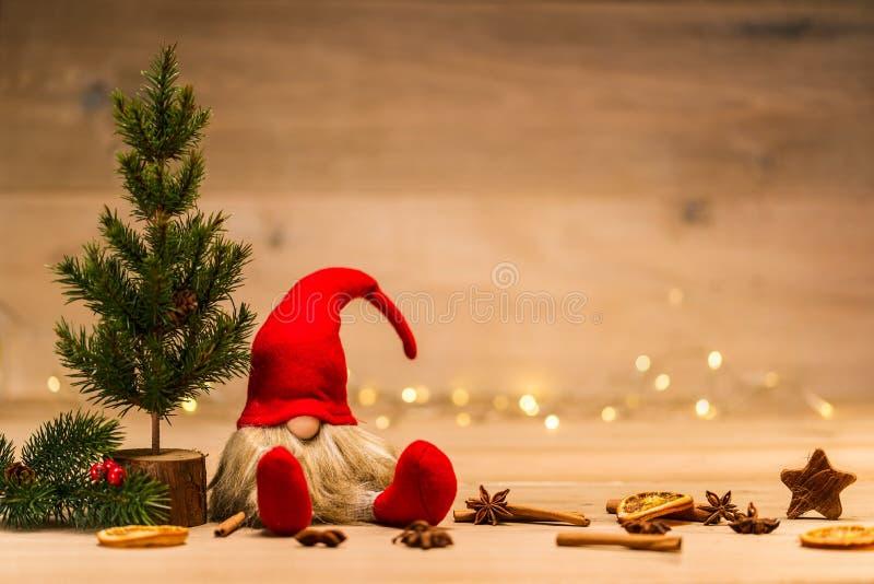 Tad de la Navidad que se sienta al lado de árbol de abeto y de la decoración de Navidad en f imagenes de archivo