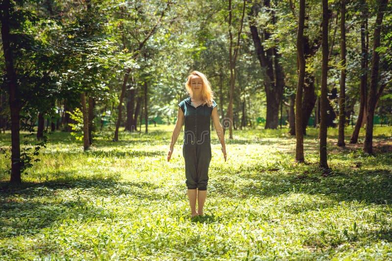 Tadasana 瑜伽asanas本质上 瑜伽摆在每天 实践的年轻女人 眼镜蛇室外公园射击体育运动主题瑜伽 库存照片