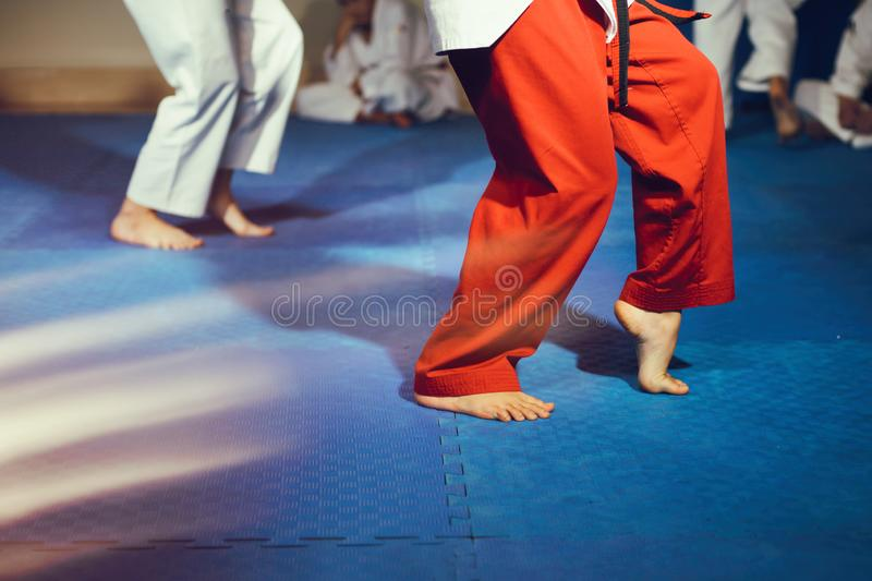 Taekwondo athletes bare feet martial arts movement on floor. Two people doing taekwondo martial art movement on floor low section bare feet, focus on foreground stock photography