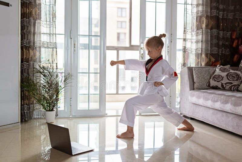 Taekwondo girl in kimono with white belt exercising at home in living room. Online education during coronavirus covid-19 lockdown royalty free stock photography