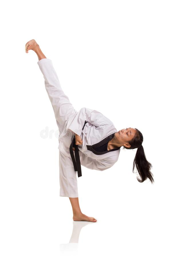 Taekwondo high kick female. Taekwondo girl high kick, full length portrait isolated over white background royalty free stock images