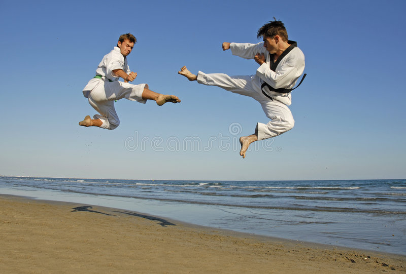 Taekwondo, kickboxing. Training of the two young men on the beach: taekwondo stock image