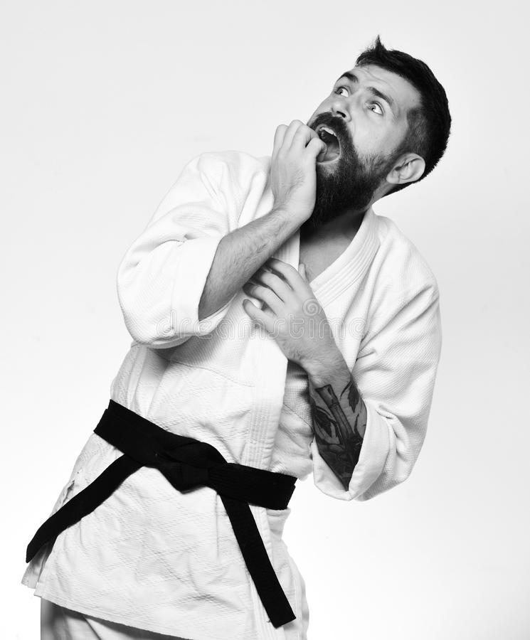 Taekwondo master with black belt bites nails in fear. Man with beard in white kimono on white background. Karate man with scared face in uniform. Oriental royalty free stock photos