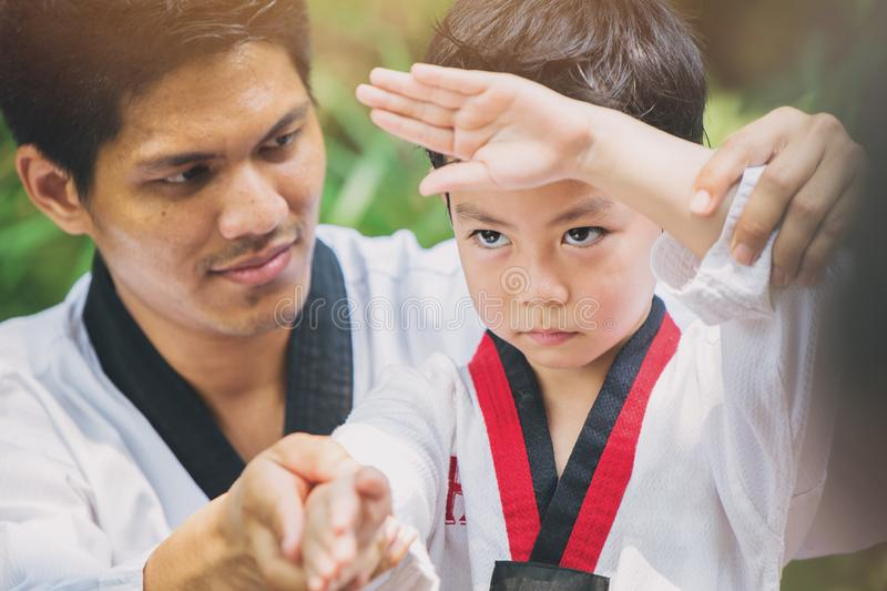 Taekwondo master black belt teaching kid to fight guard. Father and son relationship royalty free stock photography